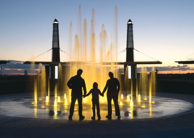 Family admiring fountain at night